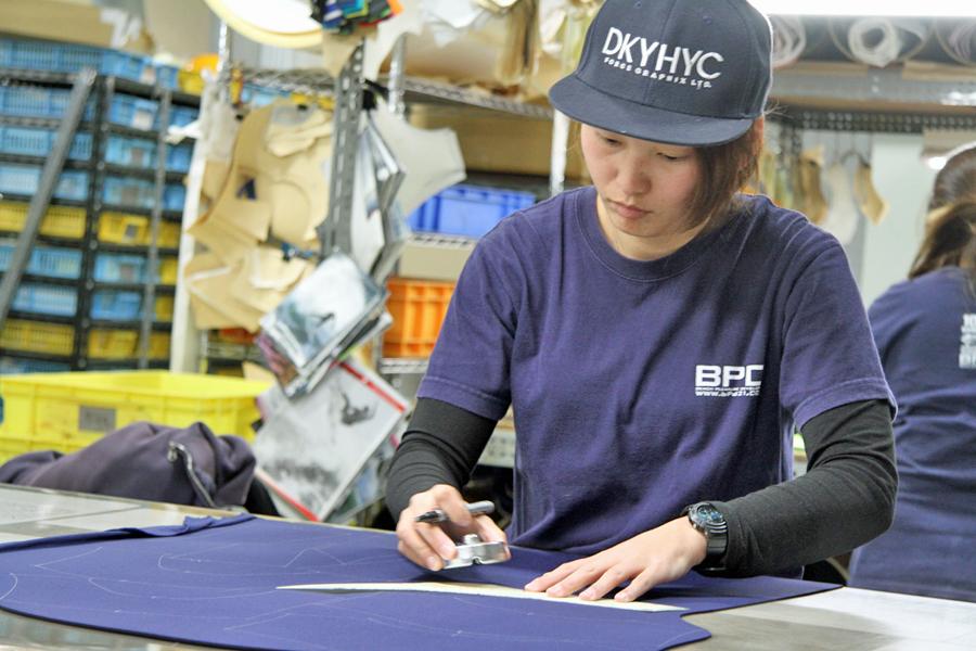 型紙に合わせてウエットスーツの原反をパーツごとに切り分ける作業